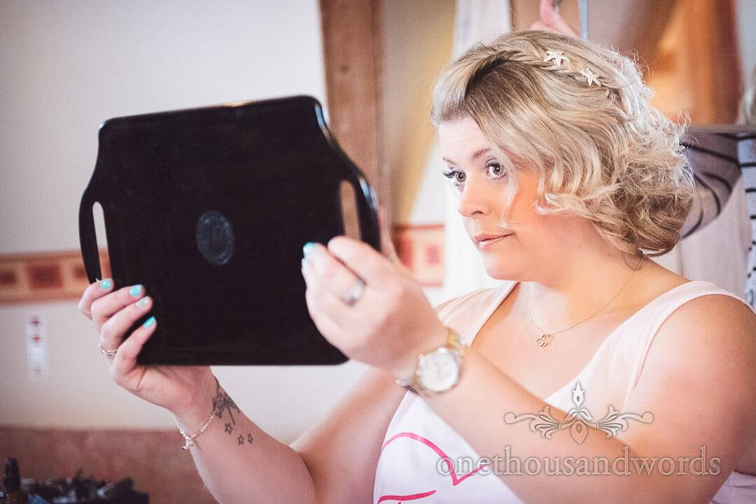 Bridesmaid examines wedding make-up in mirror on wedding morning in Swanage, Dorset