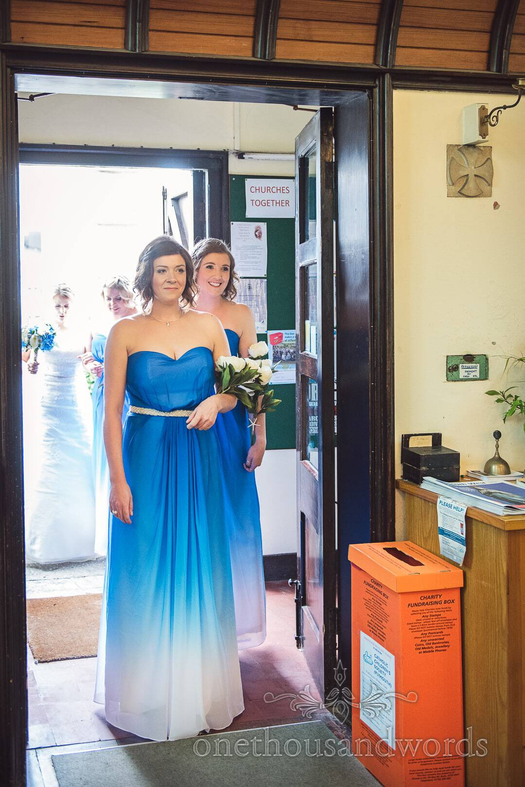 Bridesmaids in blue and white graduated bridesmaids dresses enter church wedding ceremony