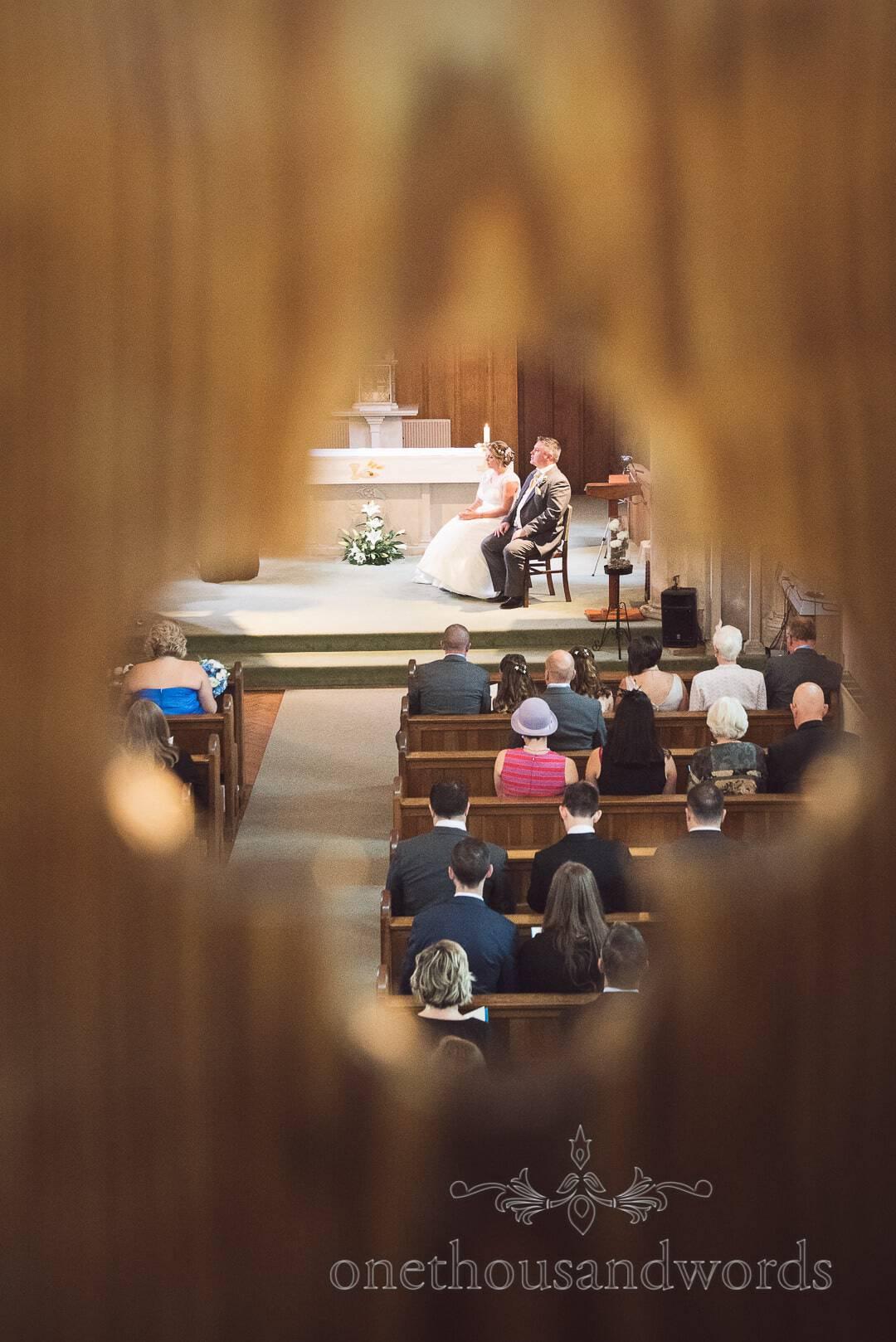 Catholic wedding ceremony photographed through wooden detail hole