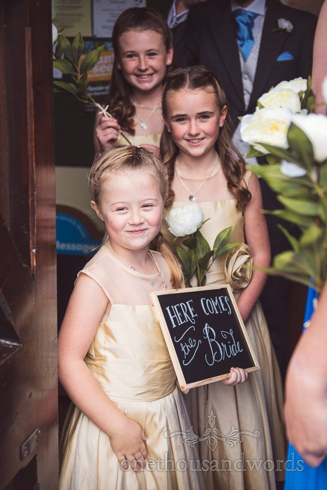 Cheeky flower girls in gold dresses with chalkboard sign look out of church doorway