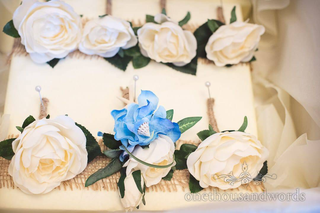 Cream silk wedding flowers with blue and shell detail for seaside themed wedding
