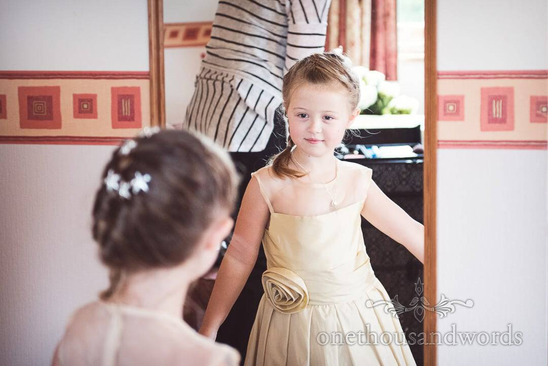 Cute flower girl in dusty gold dress looks in mirror during bridal preparation photographs