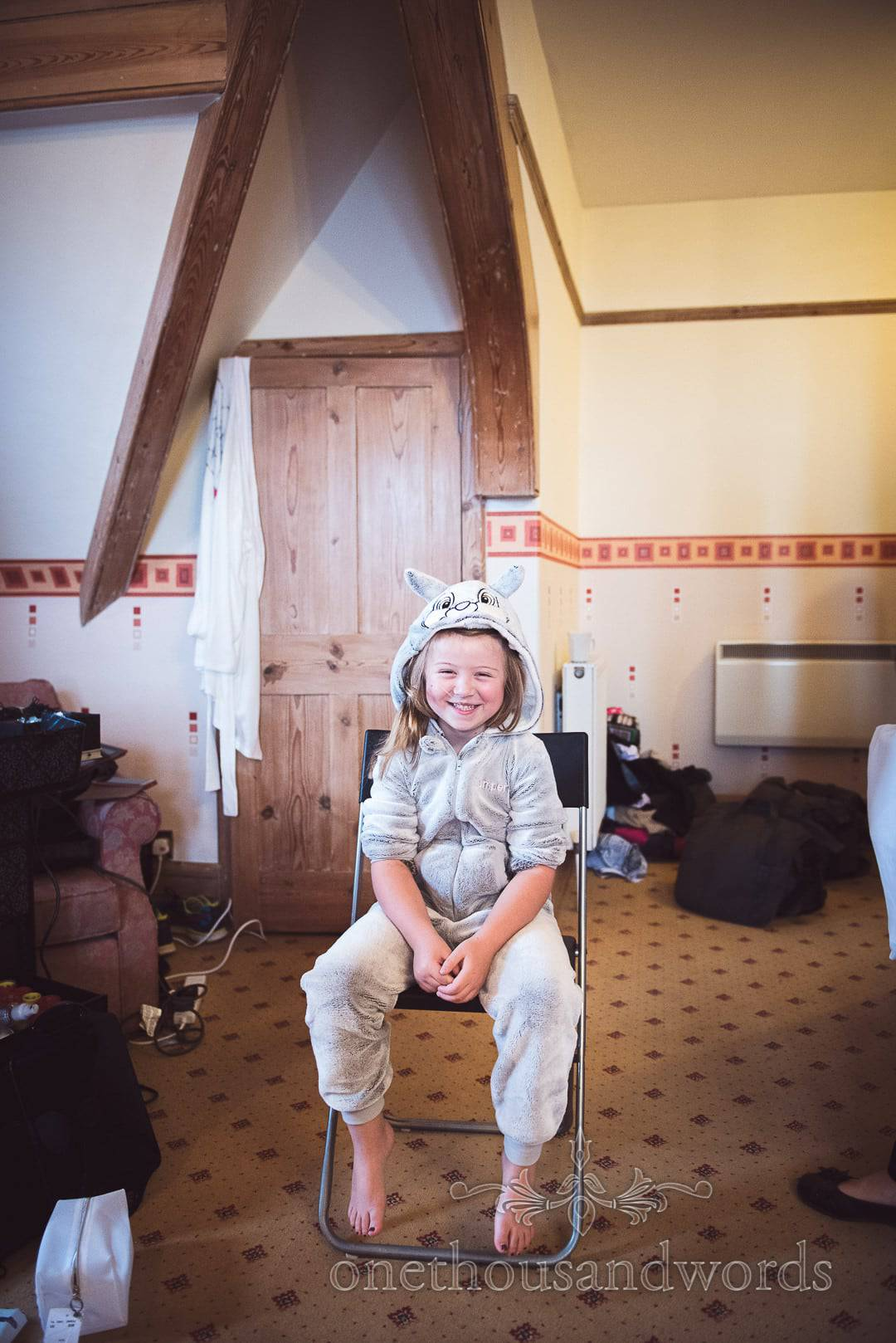 Flower girl wears bunny rabbit onesie on wedding morning in Swanage Hotel room