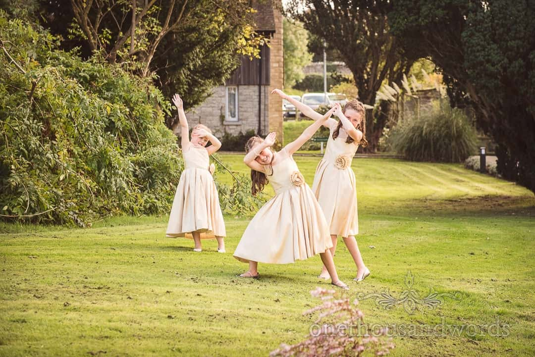 Flower girls in dusty gold dresses dabbing in gardens at Purbeck House Hotel Wedding