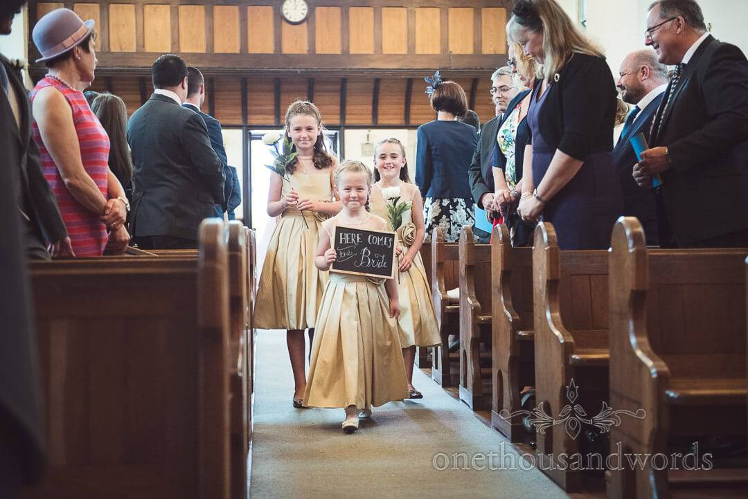 Flower girls in gold dresses carry Here Comes The Bride sign and flowers up the aisle