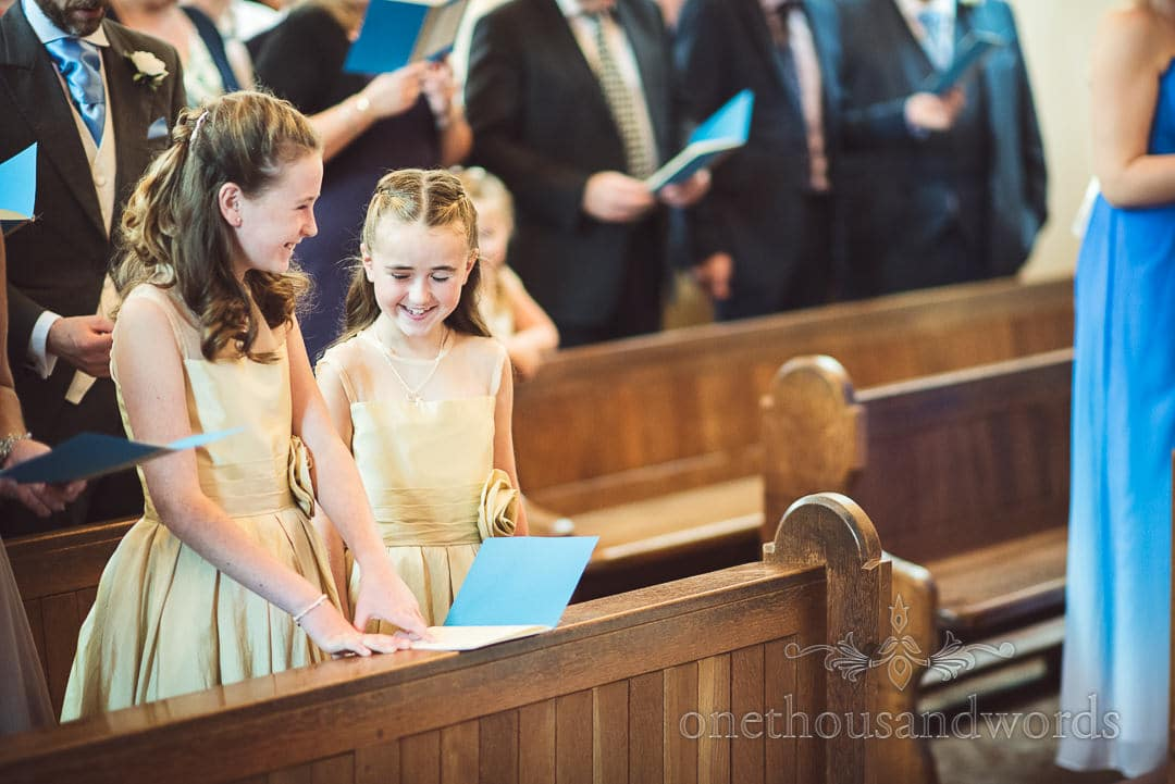 Flower girls laughing in dusty gold dresses in pews at Catholic Church wedding
