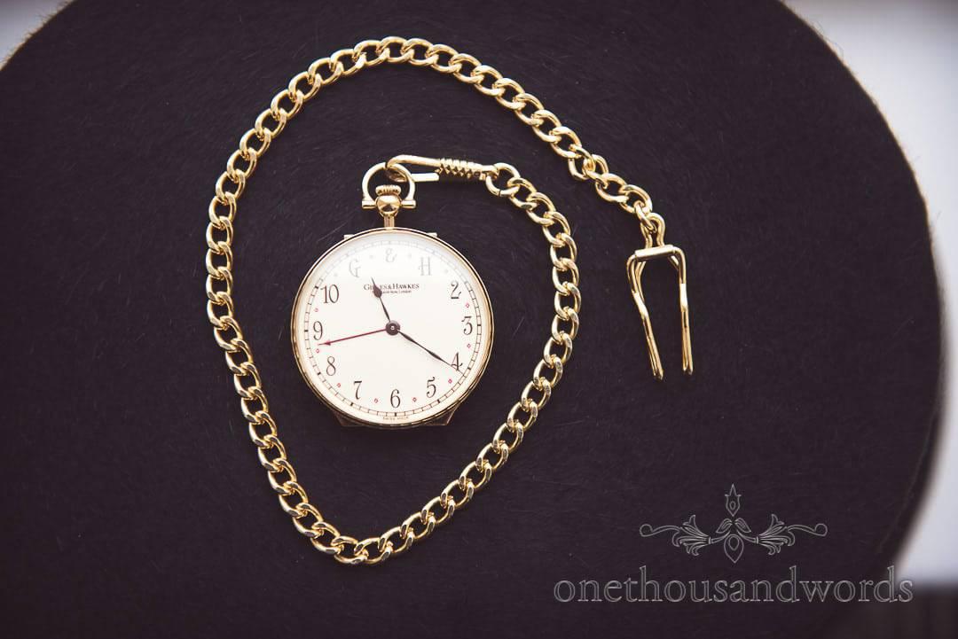Gold G & H pocket watch on top hat felt Grooms wedding detail photograph