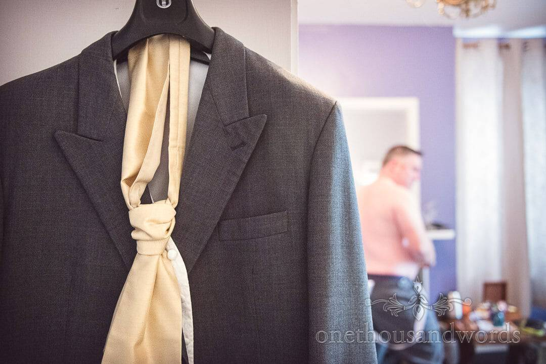 Grey wedding suit on hanger with gold cravat as groom prepares for wedding