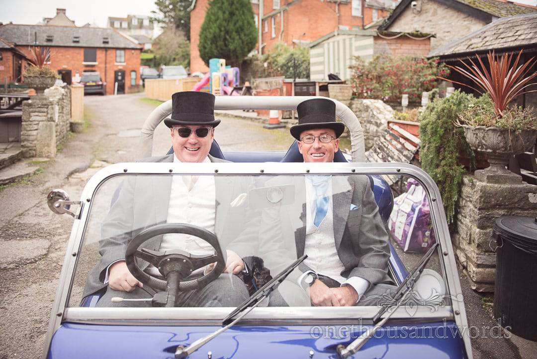 Groom and best man in top hats ride in VW beach buggy on wedding morning