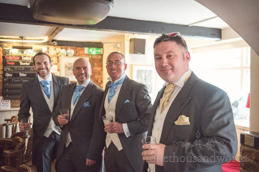 Groom and groomsmen drinking in pub on wedding morning in Dorset