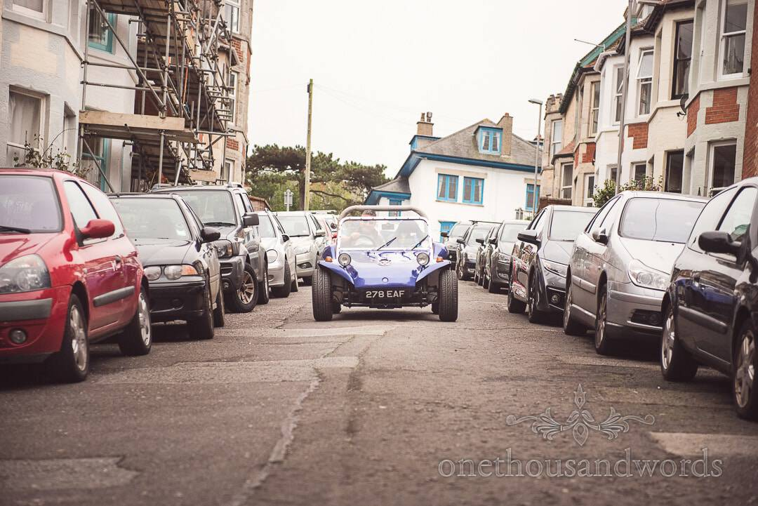 Groom drives blue VW beach buggy around the streets of Swanage on wedding morning