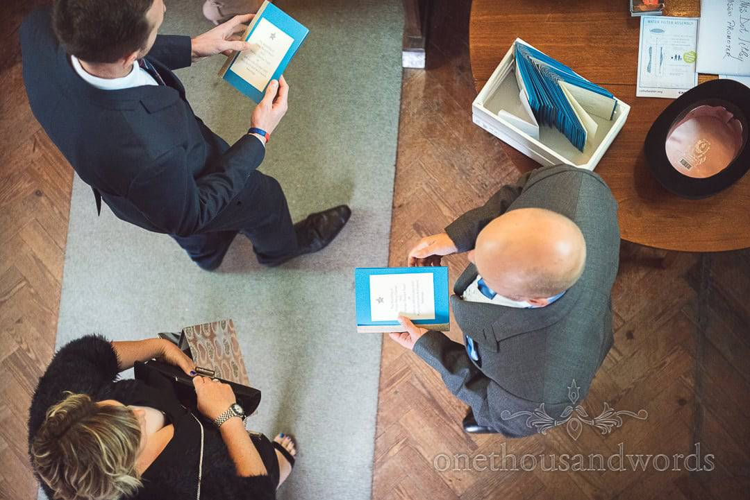 Groomsman hands out blue orders of service to guests at Church wedding