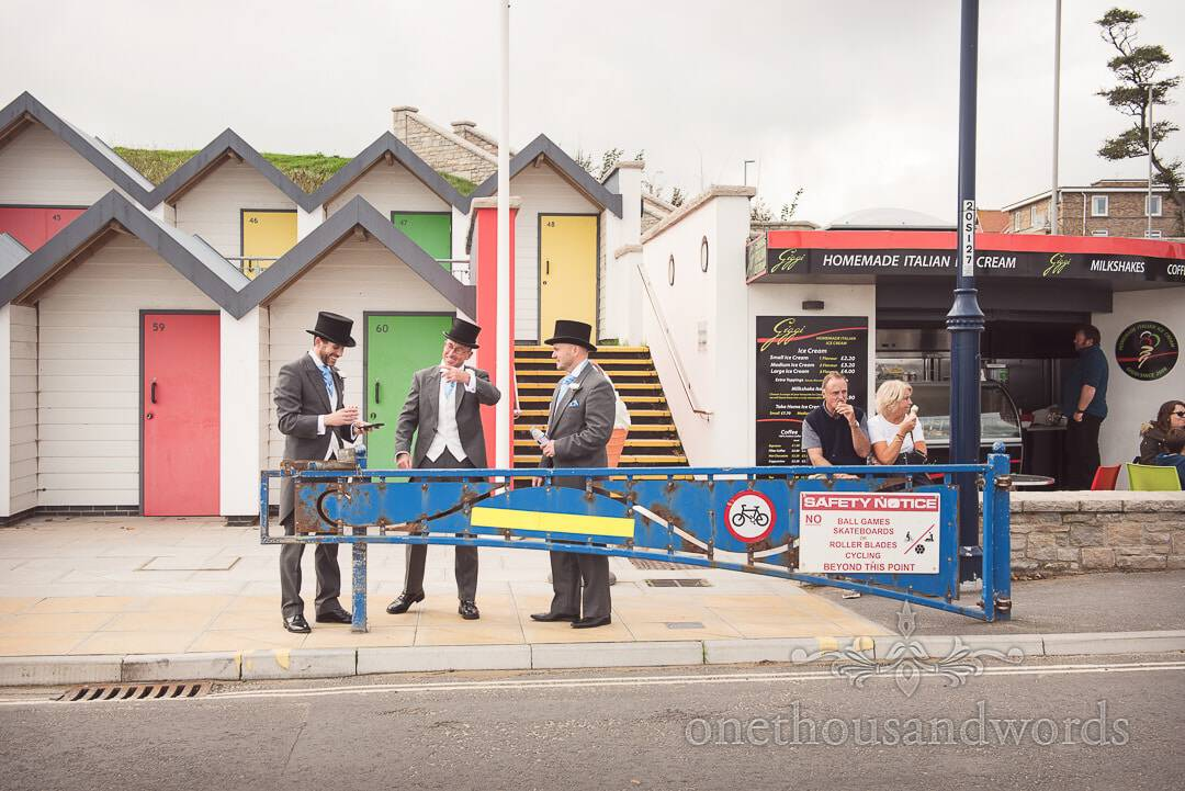 Groomsmen in top hats and tails on Swanage seafront by beach huts