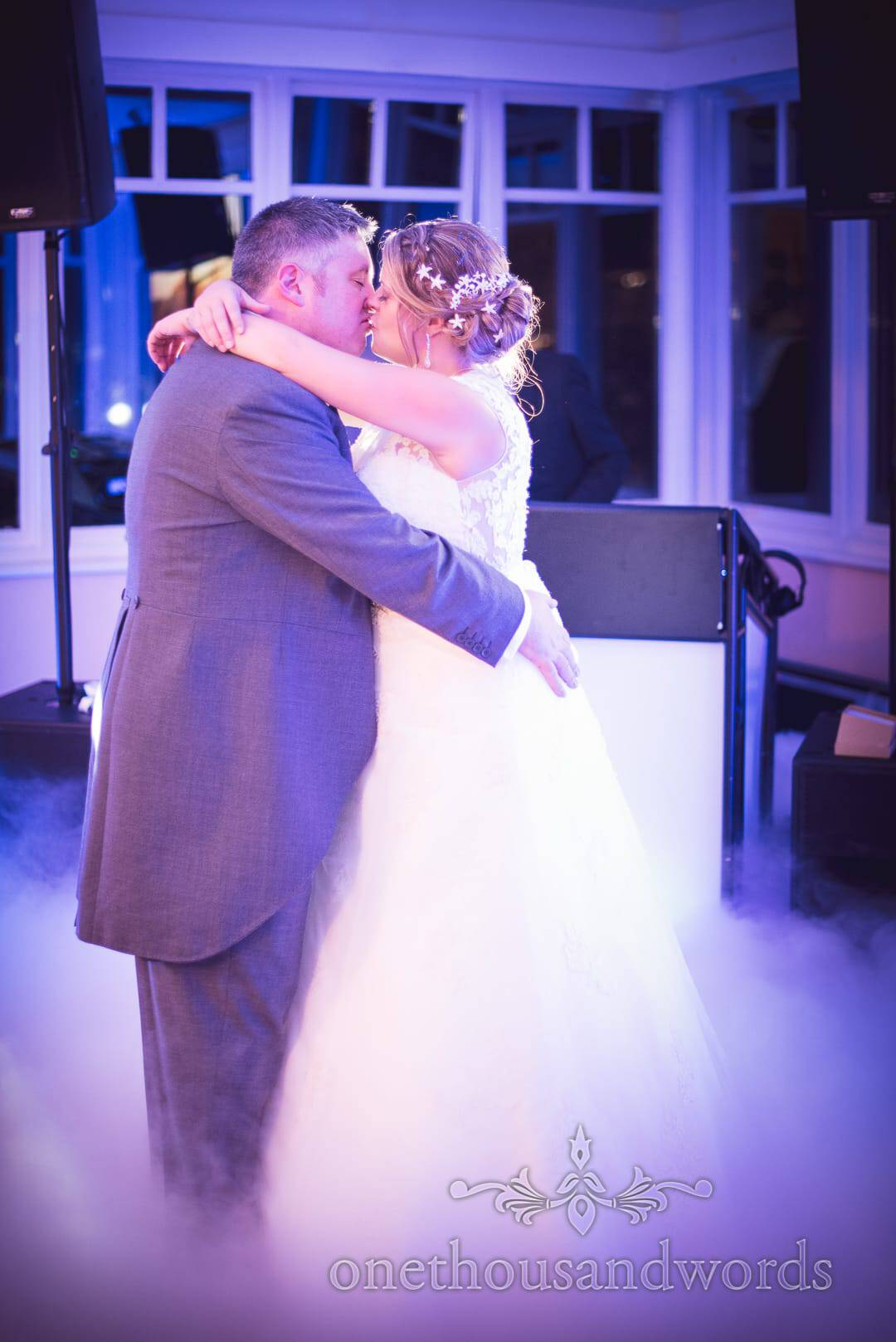 Newlyweds take their first dance on smokey dance floor at Swanage Hotel wedding photographs