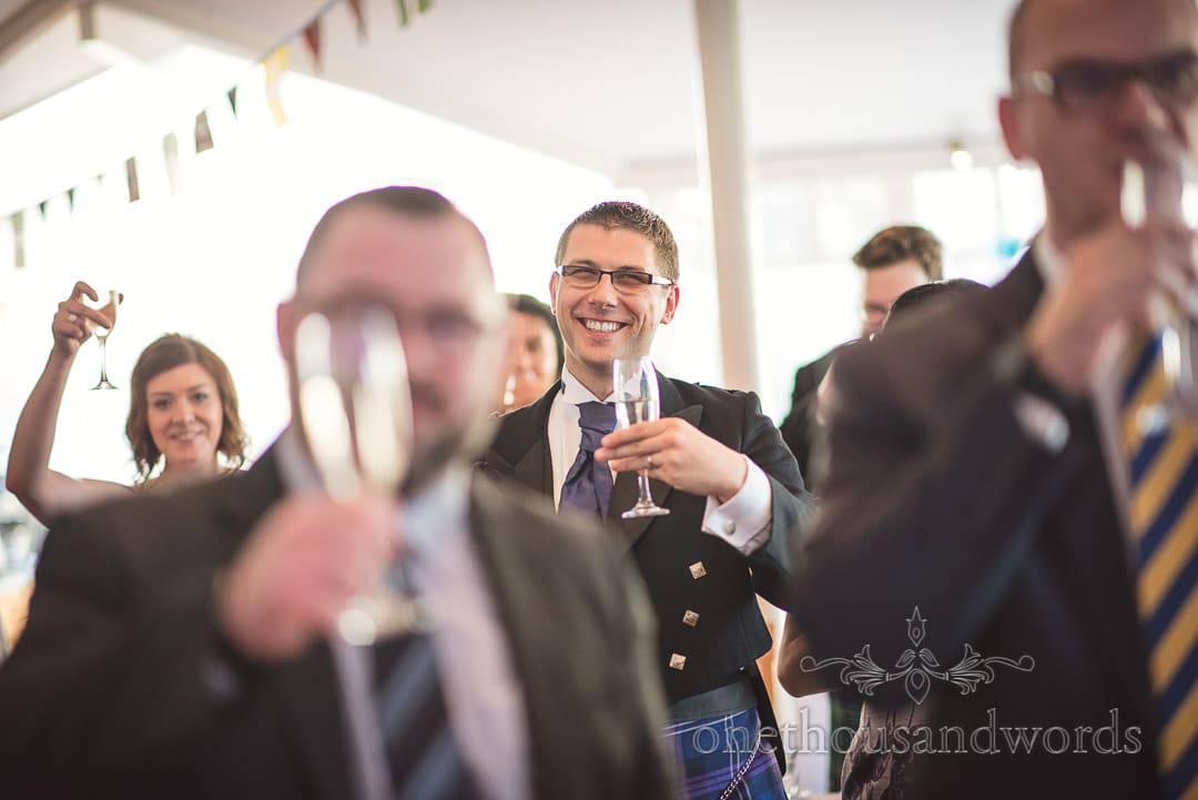 Scottish wedding guest in kilt raises a glass during wedding speeches toast