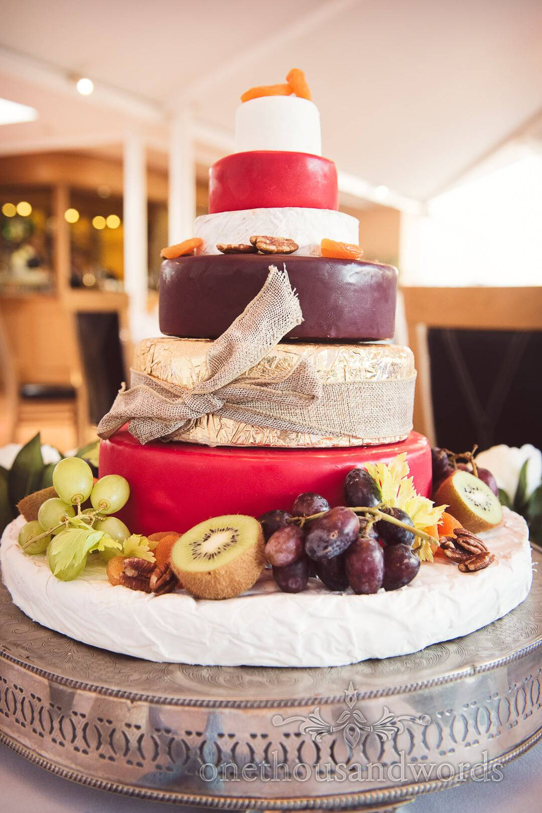 Six tier Cheese wheel wedding cake with fruit and nuts and hessian bow
