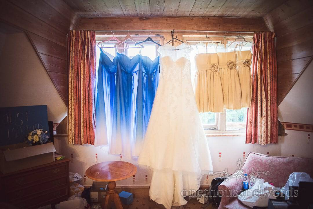 Wedding dress hangs with blue bridesmaids dresses and gold flower girls dresses