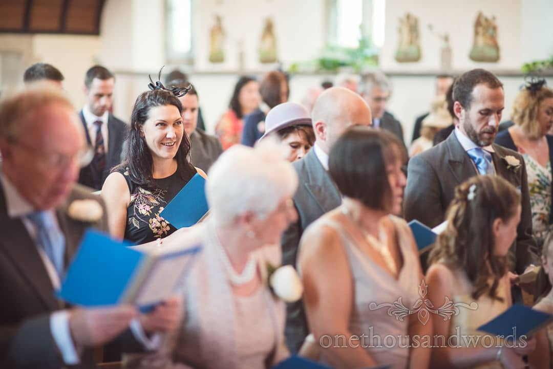 Wedding guest in black fascinator singing at Swanage Catholic Church wedding ceremony