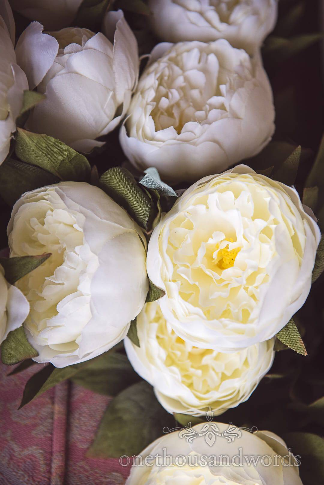 white and cream silk wedding flowers with green foliage detail photograph