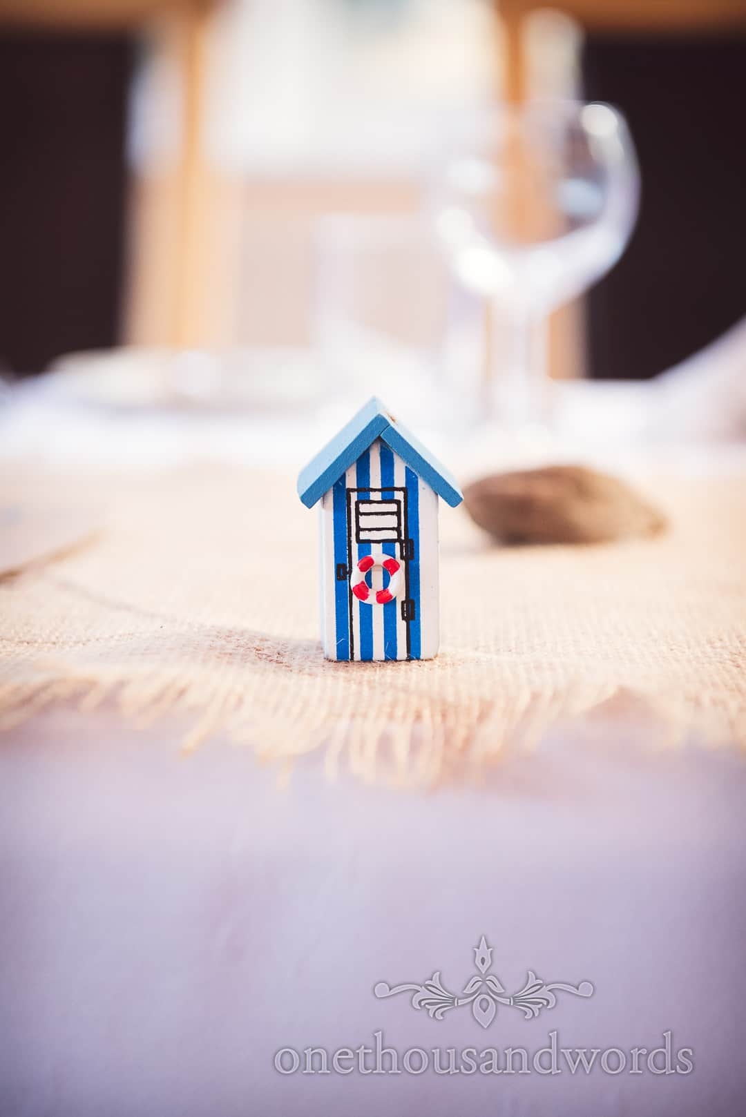 Wooden beach hut table decoration at sea side themed wedding in Dorset