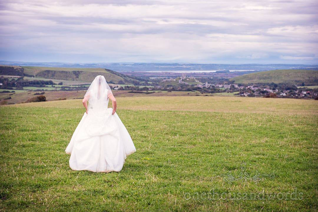 Bride looks out towards Corfe Castle from Countryside wedding