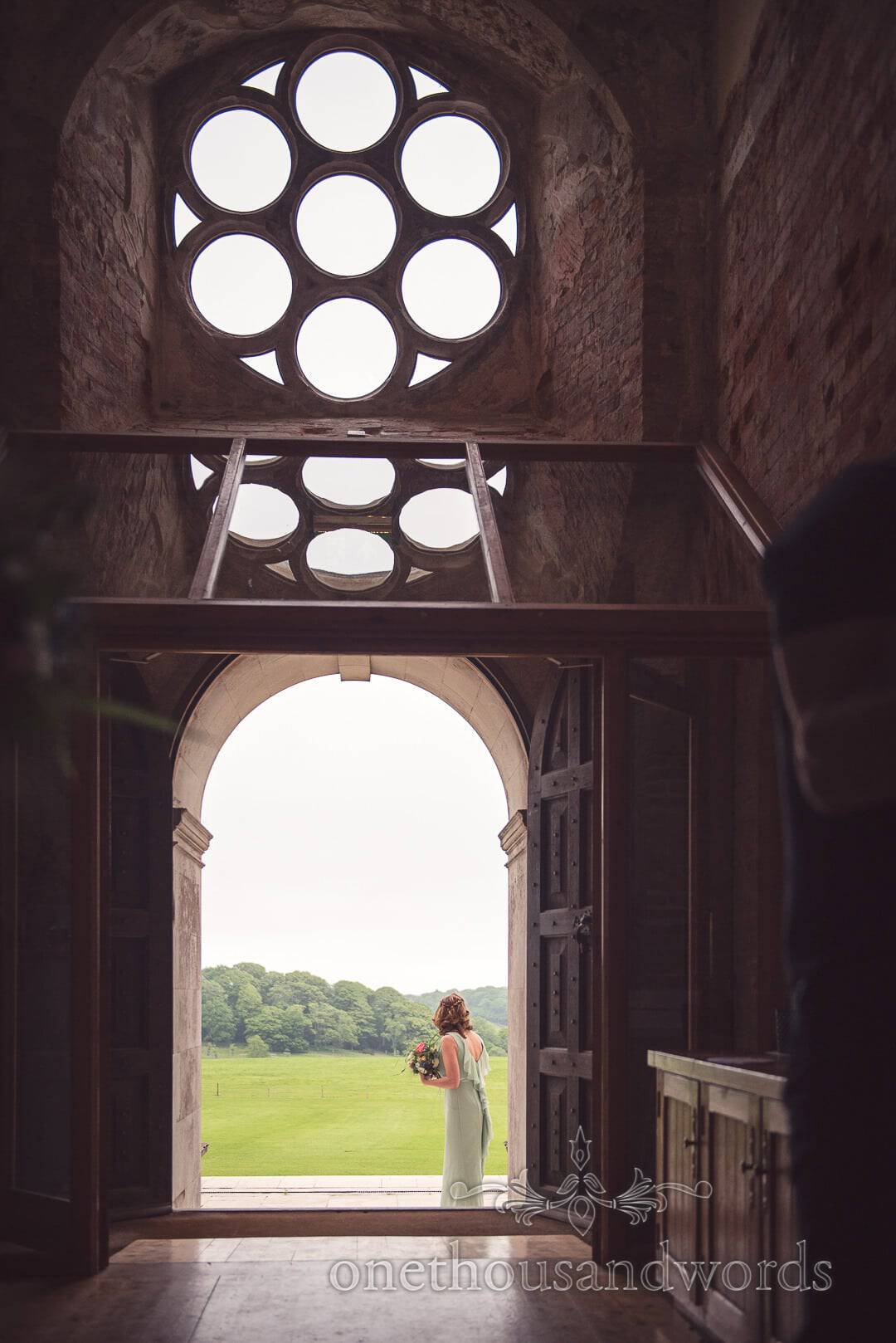 Bridesmaid awaits the arrival of bride at Lulworth Castle wedding