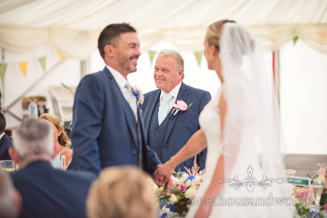 Father of the bride looks at daughter during speech at countryside wedding