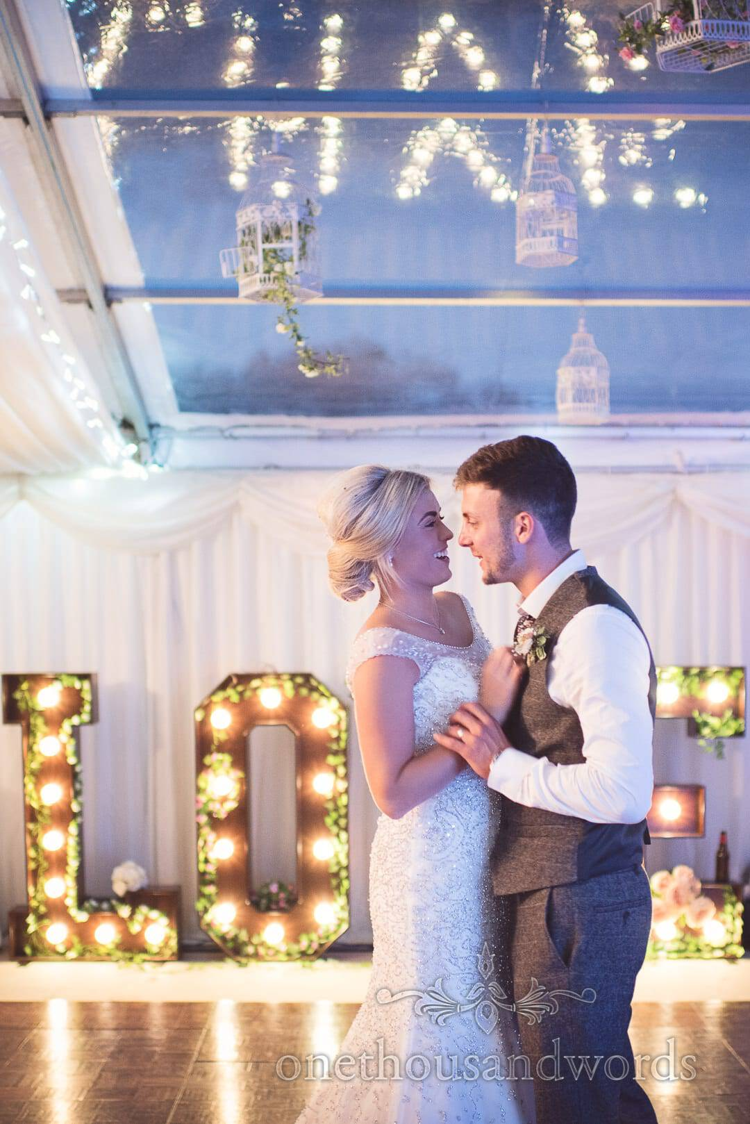 Newlyweds take their first dance in marquee at Purbeck farm wedding