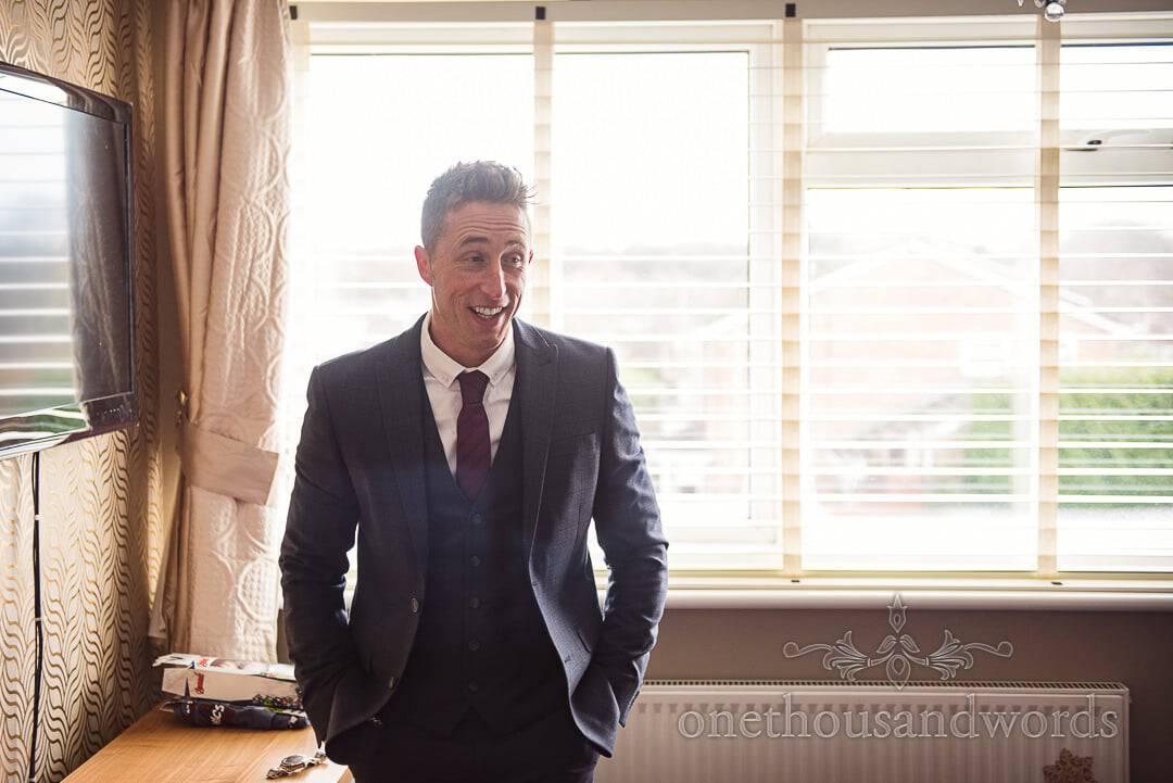 Backlit Groomsman laughs during groom preparation photographs on wedding morning