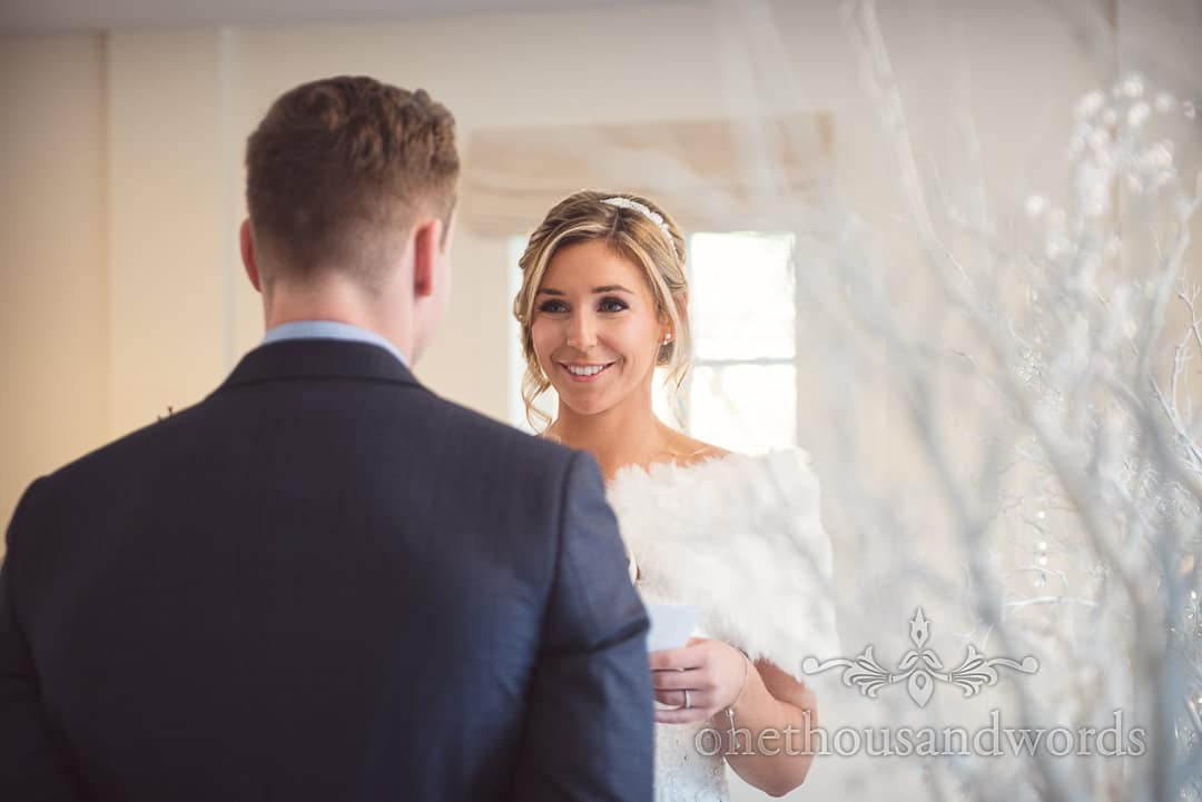 Beautiful winter bride smiles at groom as she reads her wedding vows at The Italian Villa