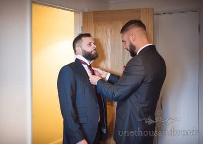 Best man helps groom with his tie before Italian Villa wedding photos