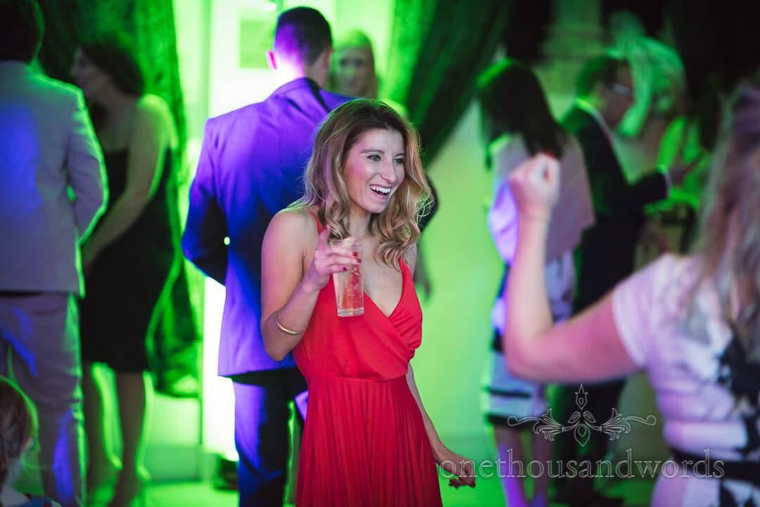 Blonde wedding guest in red dress dances at Italian Villa Wedding Venue photographs