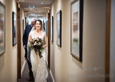 Bride and father make way along hotel corridor before Italian Villa wedding