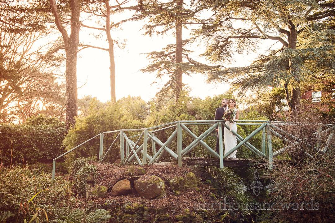 Bride and groom on bridge in gardens at Italian Villa wedding photos