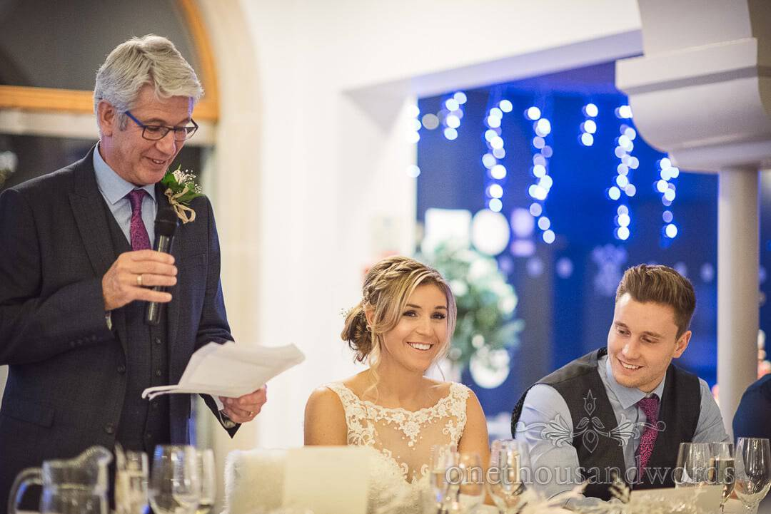 Bride and groom smile as Father of the bride gives wedding speech at The Italian Villa