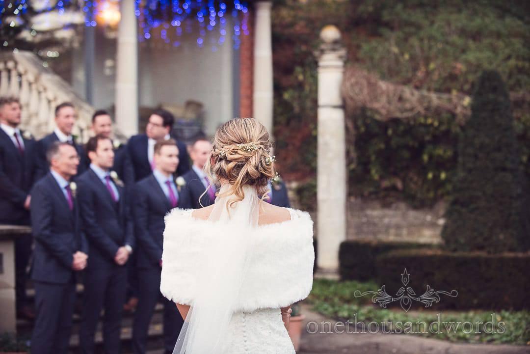 bride in white fur shrug watches groomsmen group photographs at The Italian Villa