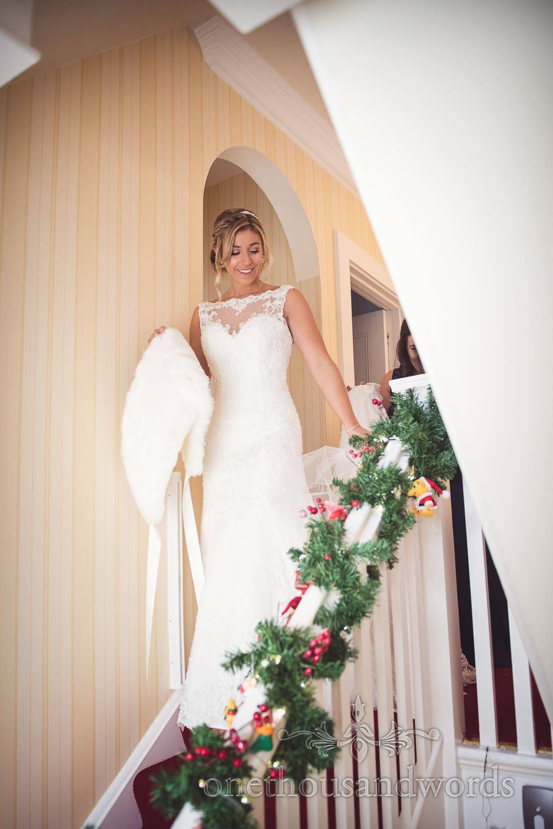 Bride in white wedding dress descends the stairs on Christmas wedding morning