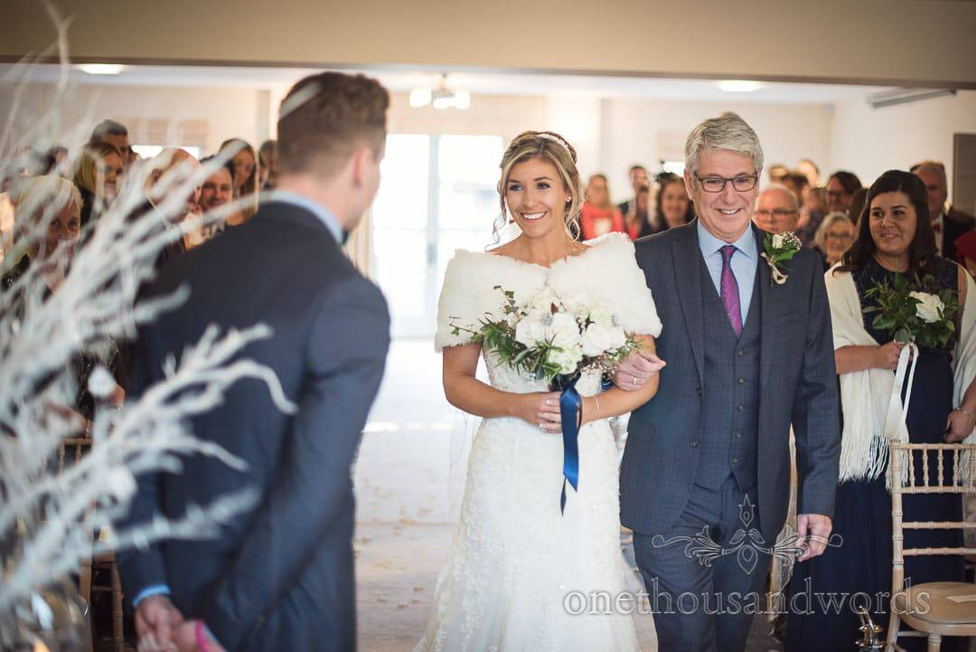 Bride is walked down the aisle at winter wonderland wedding at The Italian Villa in Poole