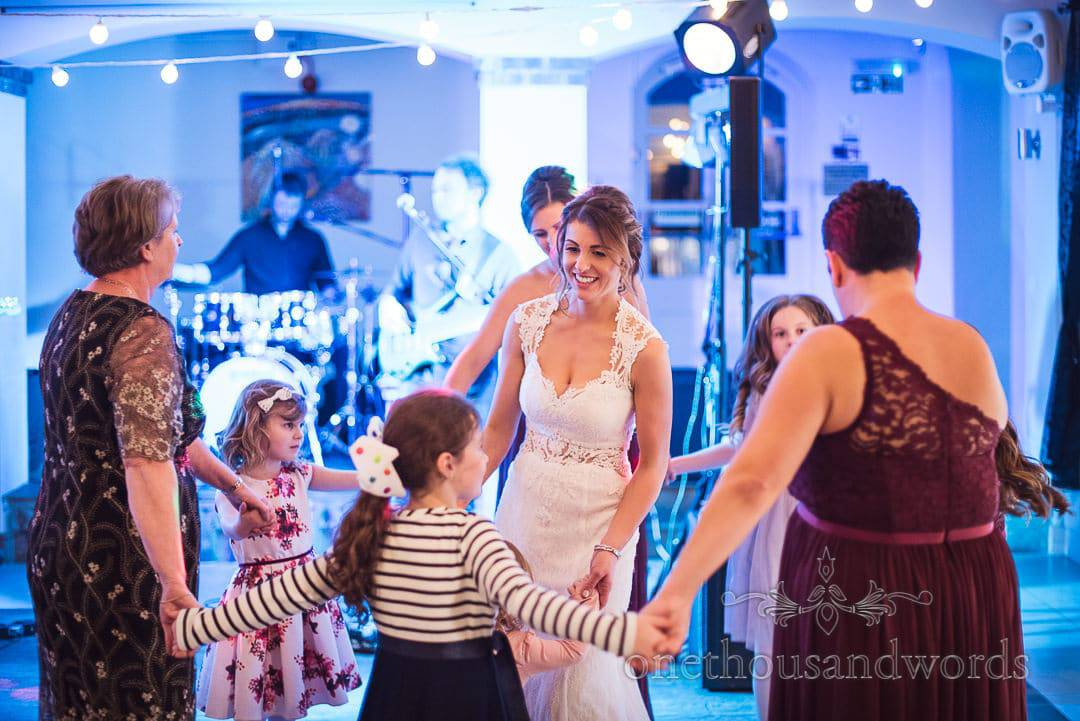 Bride, mother of the groom and bridesmaid dance with children at Italian Villa wedding photos