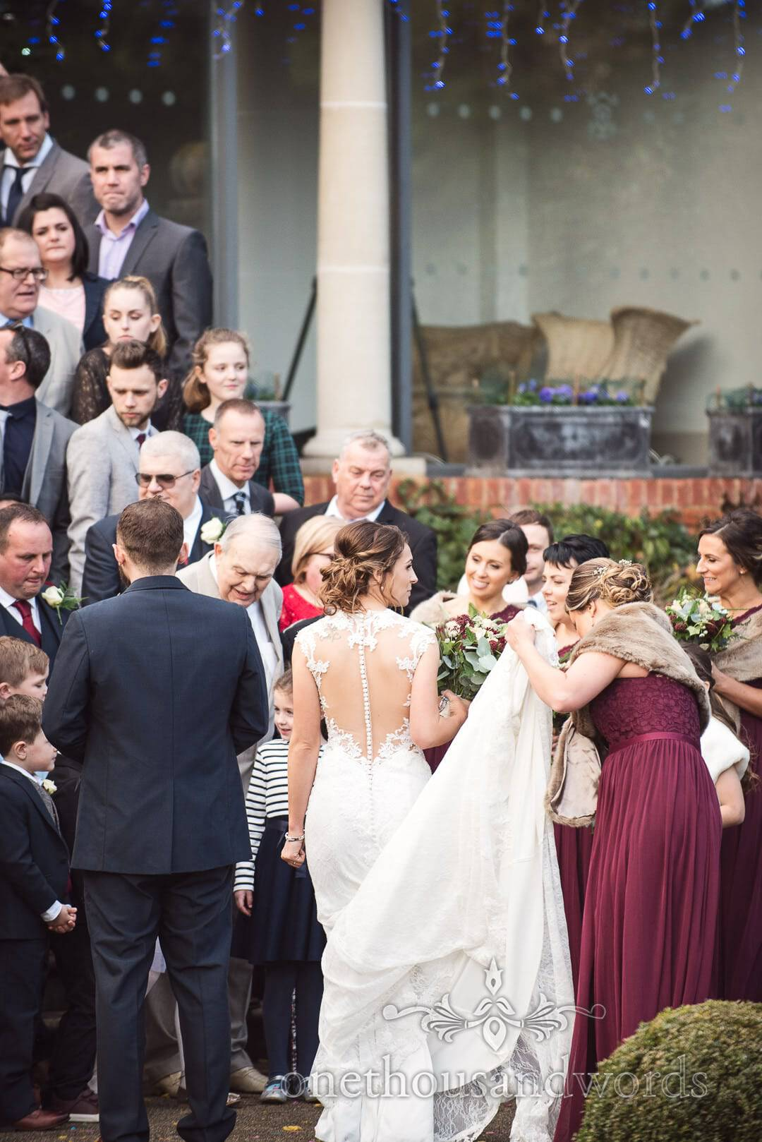 Bride with groom and bridesmaids as guest gather for group photograph at Italian Villa wedding photos
