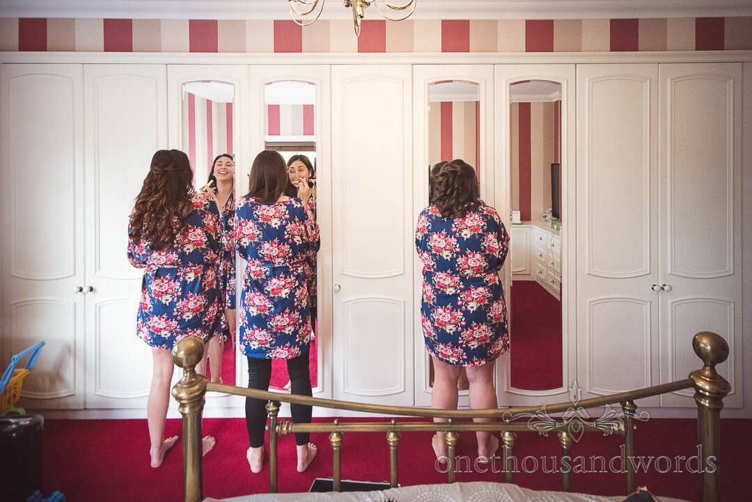 Bridesmaids wear matching floral gowns apply wedding make up in wardrobe mirrors