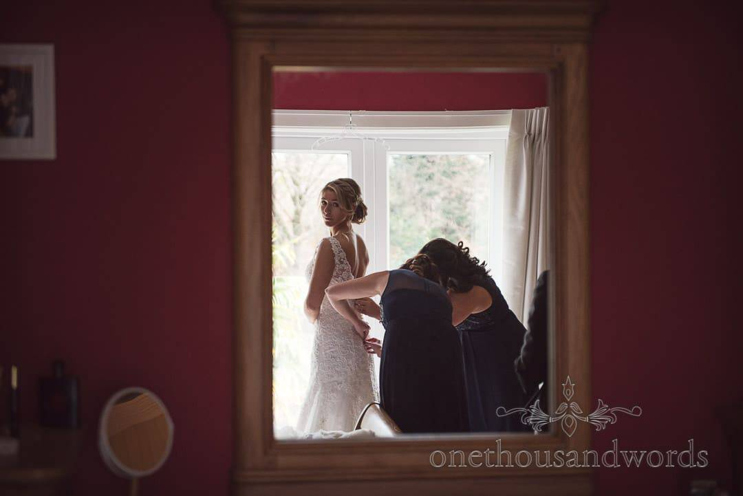 Documentary wedding photograph of Bride in mirror as buttoned into wedding dress by bridesmaids