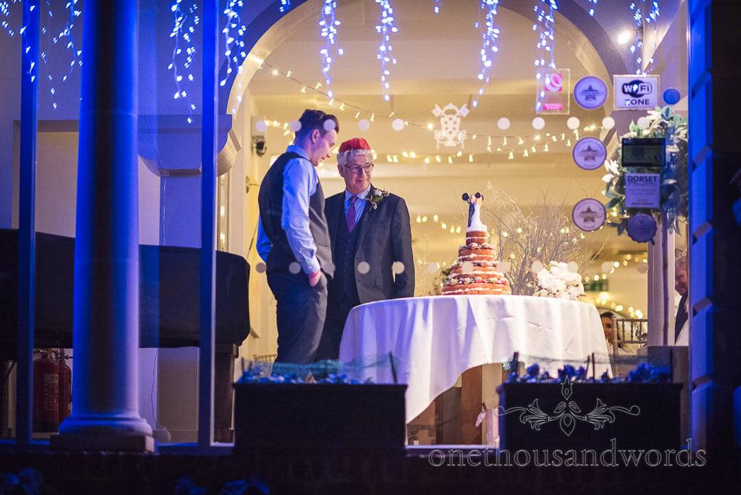 Father of the bride and groom with blue lights inspect wedding cake at The Italian Villa