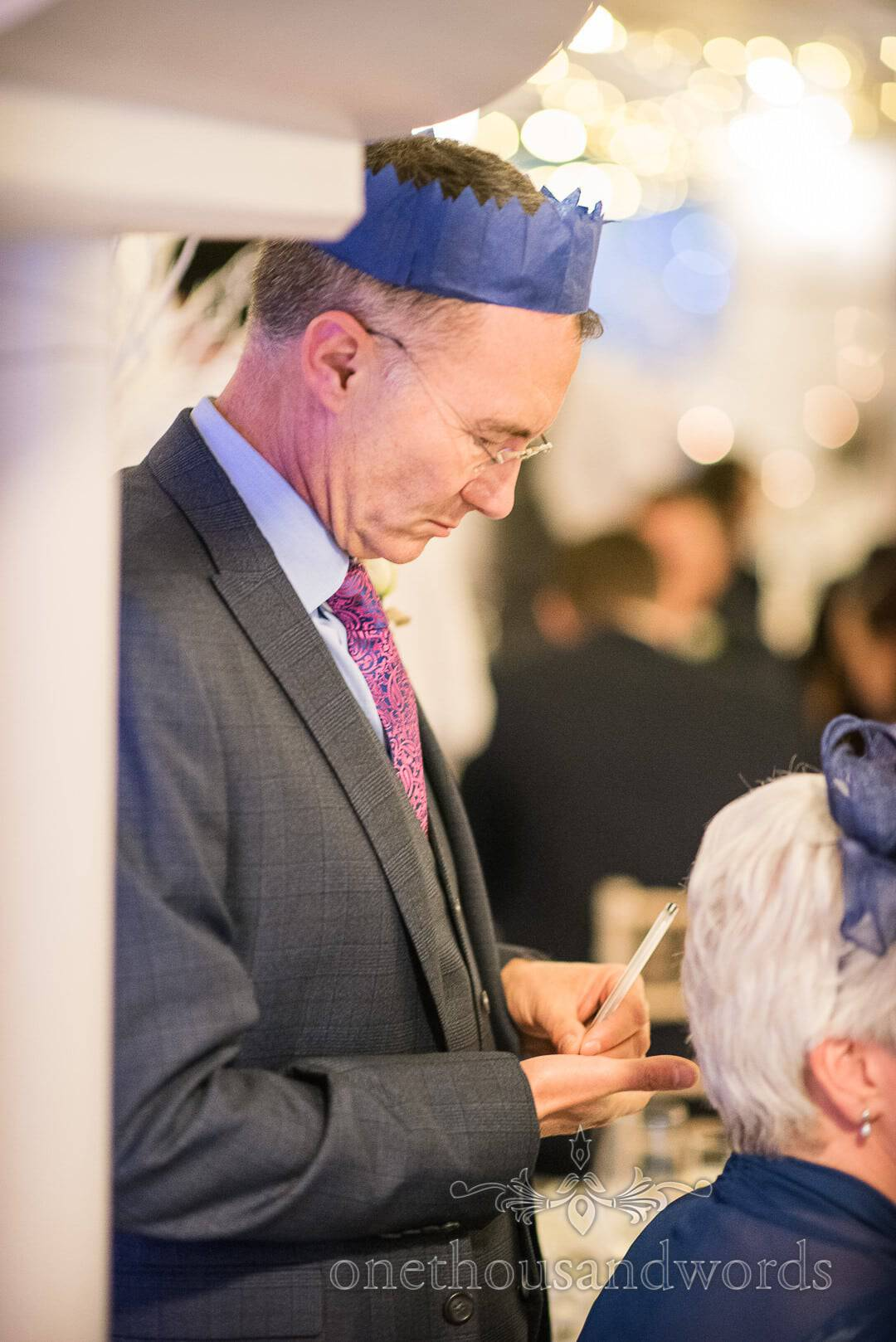 Father of the groom in Christmas party hat takes nots on wedding proceedings