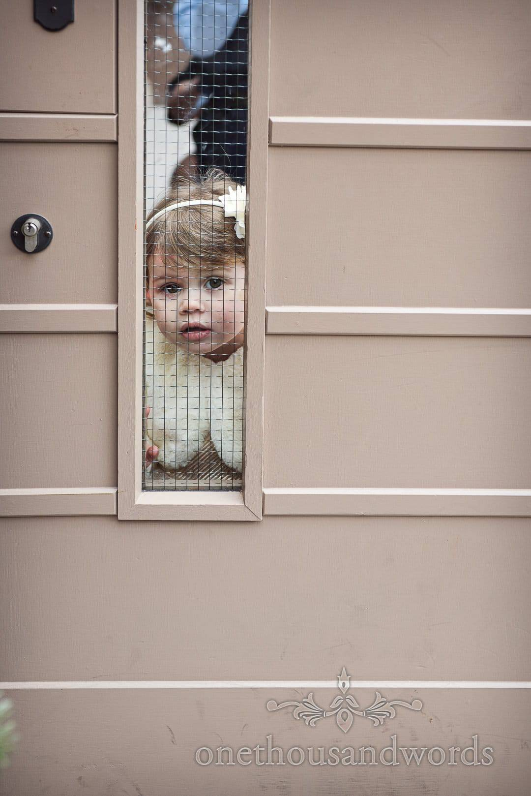 Flower girl looks through door glass before Italian Villa, Dorset wedding ceremony