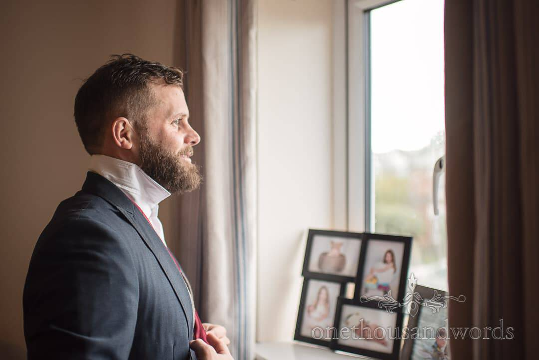 Groom looks out of window during morning preparations before Italian Villa winter wedding