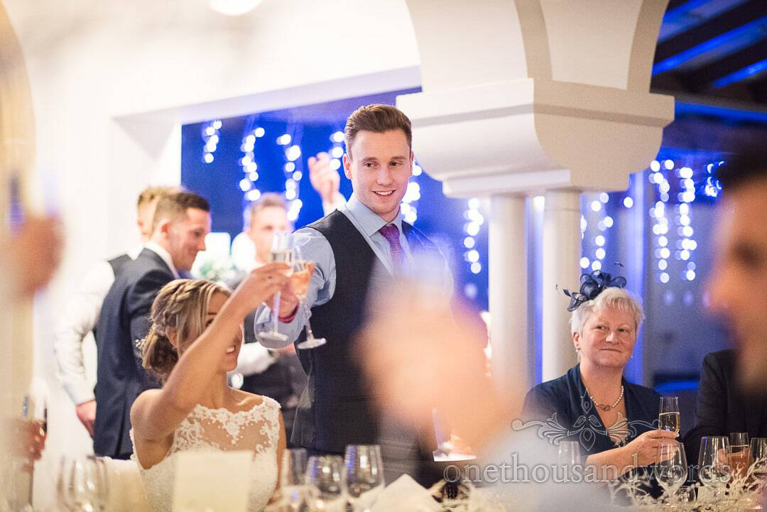 Groom raises a toast during wedding speeches at Italian Villa Christmas wedding