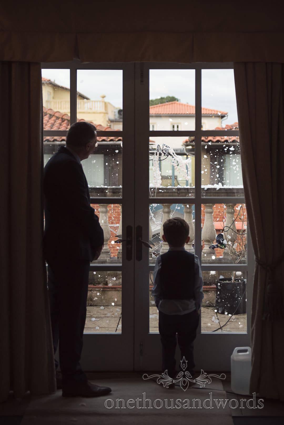 Groom's father and son watch snow machine at Italian Villa Wedding venue