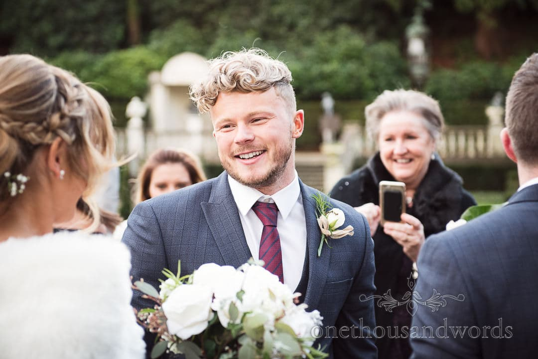 happy grooms man in blue suit with white button hole smiles at newly wed bride