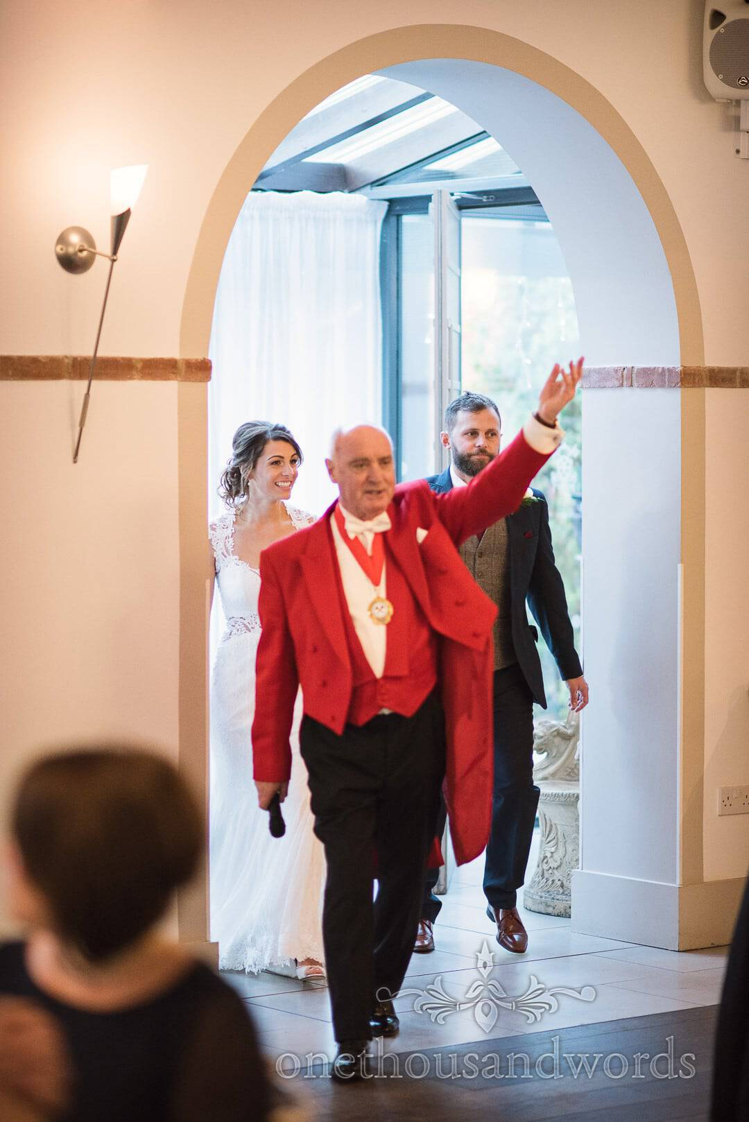Master of ceremonies asks guests to be upstanding for the entrance of the bride and groom